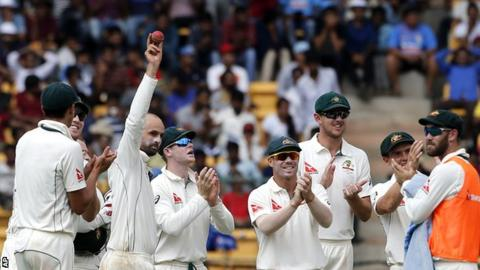 Australia spinner Nathan Lyon holds the ball up after taking his fifth wicket