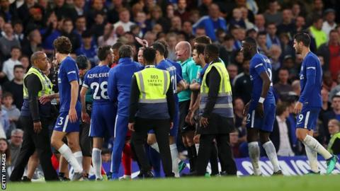 Lee Mason surrounded by Chelsea players