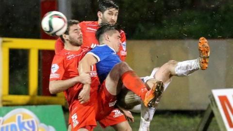 Portadown defenders Chris Ramsey and Ken Oman challenge Jimmy Callacher of Linfield