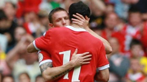 Wales captains Craig Bellamy and Ryan Giggs hug