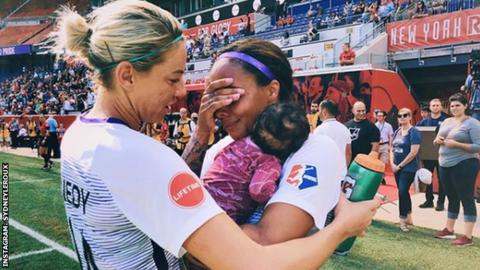 Sydney Leroux celebrates after a game with her baby and a team-mate
