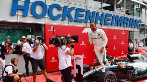 Mercedes driver Lewis Hamilton celebrates winning the German Grand Prix