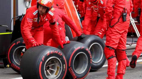 A Ferrari mechanic moves tyres