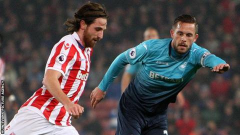 Joe Allen in action against Swansea's Gylfi Sigurdsson.