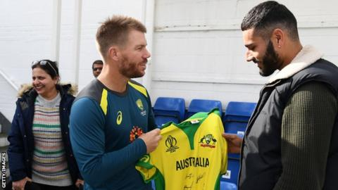 David Warner presents a signed shirt to Jaykishan Plaha, right, watched on by Plaha's mother, left