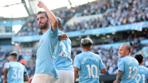 Bernardo Silva raises his fist in salute as his Man City team-mates celebrate behind him