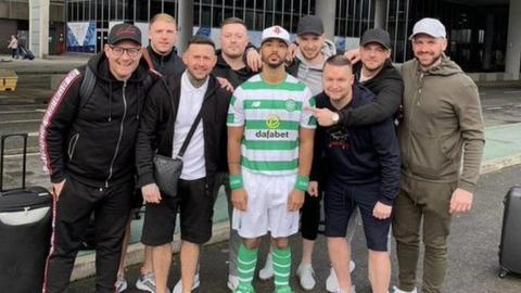 Shay Logan (centre) wearing a Celtic shirt