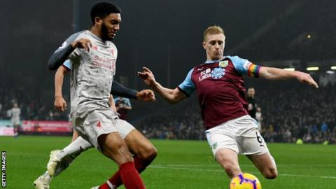 Liverpool defender Joe Gomez (left) goes to challenge Burnley captain Ben Mee (right) for the ball during a Premier League match at Anfield