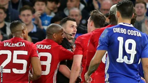 Referee Michael Oliver is surrounded by several Manchester United players after sending off midfielder Ander Herrera