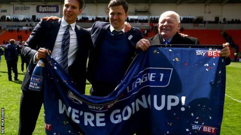 Wigan Athletic manager Gary Caldwell (centre) celebrates with chairman David Sharpe (left) and owner Dave Whelan