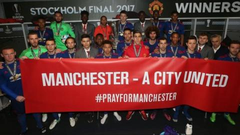 Manchester United players hold up a banner