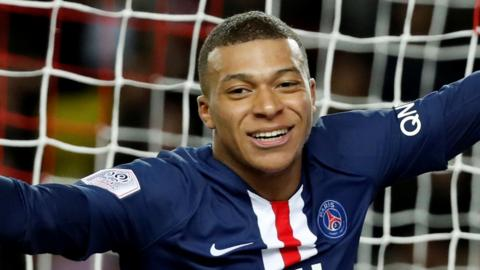 Kylian Mbappe, in close-up, turning and smiling to celebrate a goal