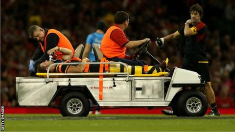Leigh Halfpenny is taken from the field on a stretcher after rupturing a cruciate knee ligament while playing for Wales against Italy in September 2015