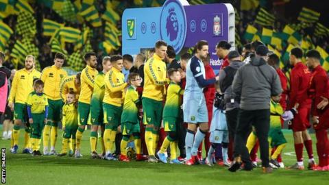 Norwich and Liverpool shake hands before their Premier League match