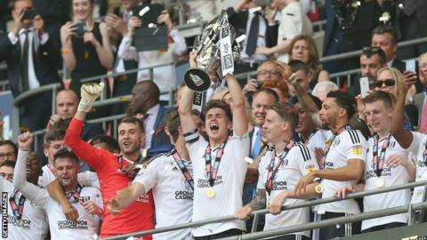 Tom Cairney lifts the Championship play-off trophy aloft at Wembley