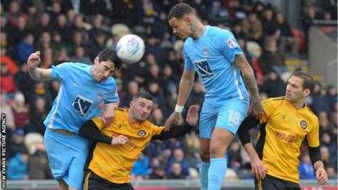 Peter Vincenti of Coventry City beats Padraig Amond of Newport County to the ball