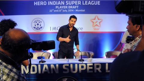 Bollywood actor John Abraham gives a thumbs up at a news conference for the Indian Super League