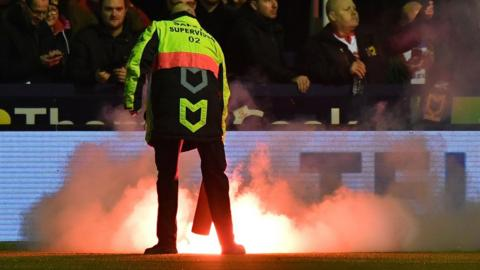 A fire had to be out at Ewen Fields following the release of the flare during the Hyde-MK Dons FA Cup first round tie