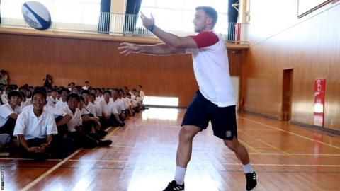 George Ford passes the ball into the crowd during the England team visit to Miyazaki Kita High School on September 11, 2019 in Miyazaki, Japan.