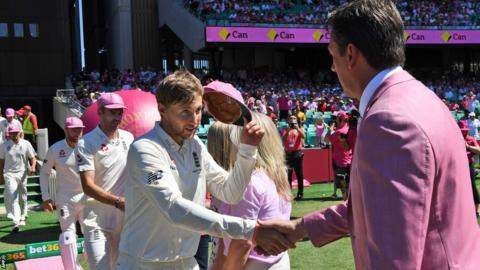 Joe Root hands his cap to Glenn McGrath