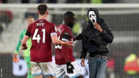 West Ham's Arthur Masuaku and Declan Rice attempt to remove a pitch invader at London Stadium on Wednesday night