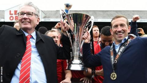 Nigel Travis lifts the 2018-19 National League trophy with Justin Edinburgh