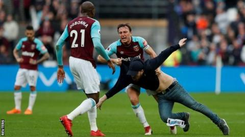 Mark Noble confronts a supporter during the match against Burnley