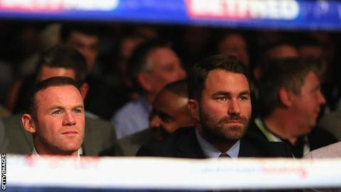 Wayne Rooney sits with Eddie Hearn ringside
