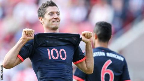 Robert Lewandowski celebrates scoring his 100th Bundesliga goal