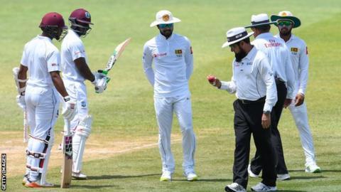Umpire Aleem Dar inspects the ball as Sri Lanka captain Dinesh Chandimal (centre) looks on