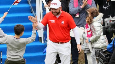 Andy Sullivan high fives a young fan at the first tee