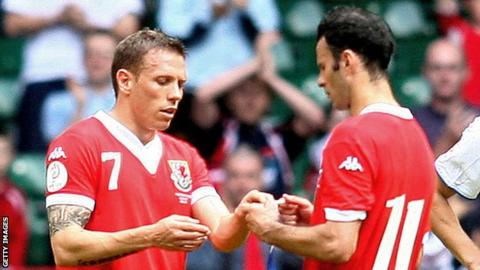 Craig Bellamy accepts the Wales captain's armband from Ryan Giggs as the Manchester United player bows out from international football in 2007