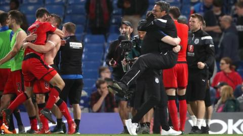 Huddersfield's players and management celebrate after securing safety
