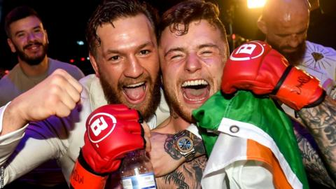 A victorious James Gallagher celebrates with his SBG team mate and UFC star Conor McGregor