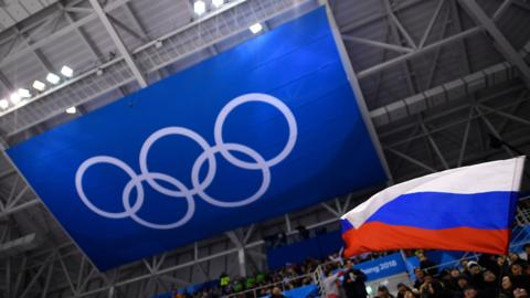 A fan waves the Russian flag beneath a banner of the Olympic rings at the 2018 Winter Olympics in South Korea