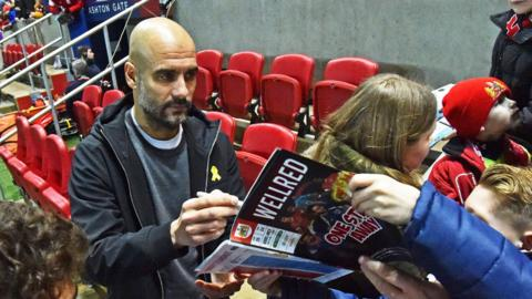 Manchester City manager Pep Guardiola signs a programme