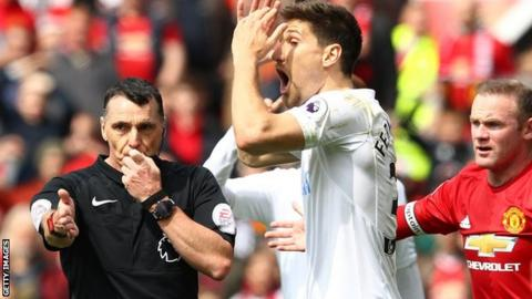 Referee Neil Swarbrick points to the spot to award a penalty to Manchester United against Swansea