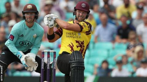 Corey Anderson hits a boundary to the leg-side as Surrey wicketkeeper Rory Burns watches from behind the stumps