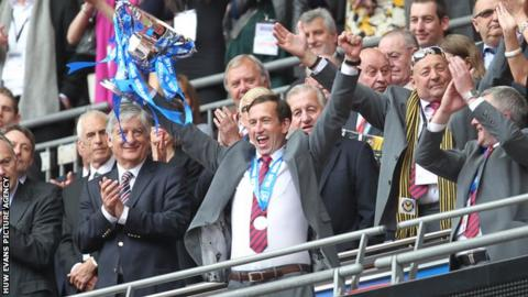 Justin Edinburgh lifts the Conference play-off trophy in the air