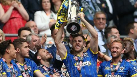 Jon Meades lfts the League Two play-off final trophy after AFC Wimbledon's 2-0 win over Plymouth Argyle