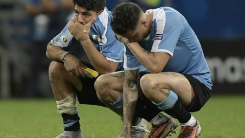 Salvador, Brazil, 29 June: Uruguay striker Luis Suarez (left) is inconsolable after missing the only penalty of a shootout defeat against Peru in the Copa America quarter-finals at the Fonte Nova Arena. (Juan Mabromata/AFP/Getty Images)