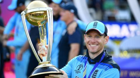 England captain Eoin Morgan smiles as he holds up the World Cup trophy