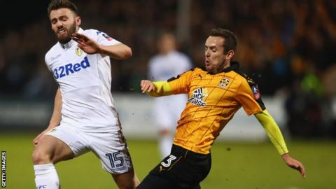 Leeds United's Stuart Dallas closes down Cambridge United defender Blair Adams (right)