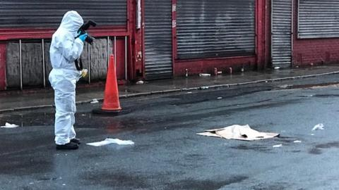 Man in forensic suit outside Anfield.