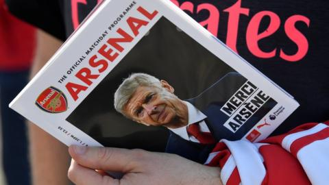 Arsenal fan holding the match day programme