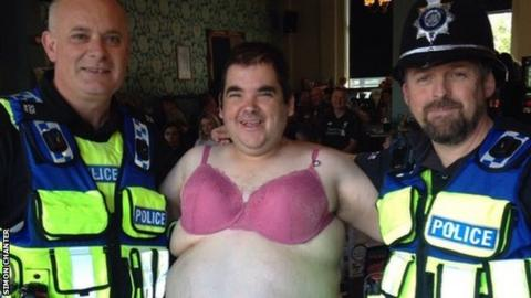 Simon Chanter in a bra with police officers after Lincoln City's match at Stevenage