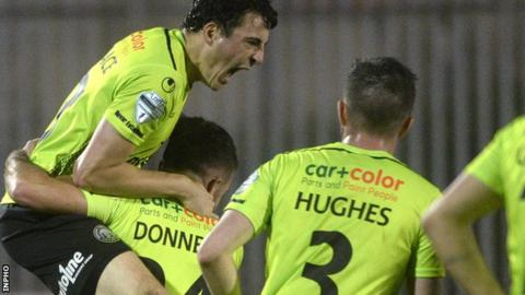 A delighted Danny Wallace leaps on Philip Donnelly after the late leveller at the Showgrounds