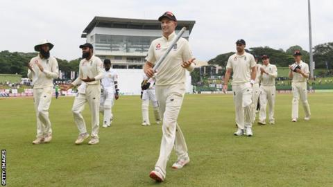 England captain Joe Root holds a stump as he leads his side off the pitch following victory over Sri Lanka in the second Test