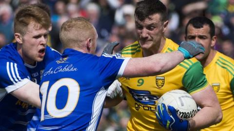 Cavan players attempt to halt the run of Donegal's Leo McLoone in the preliminary round game