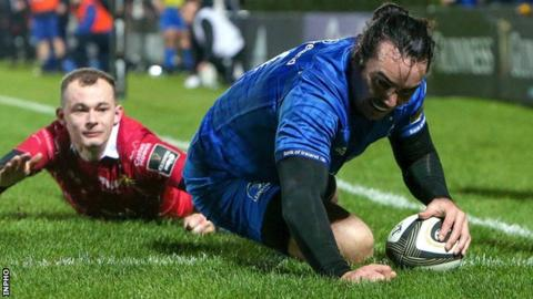Leinster's James Lowe scores a try despite the attentions of Scarlets wing Ioan Nicholas